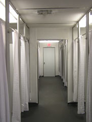 row of showers with curtains and dividers