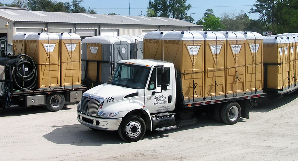 trucks with portable restrooms loaded onto flat beds