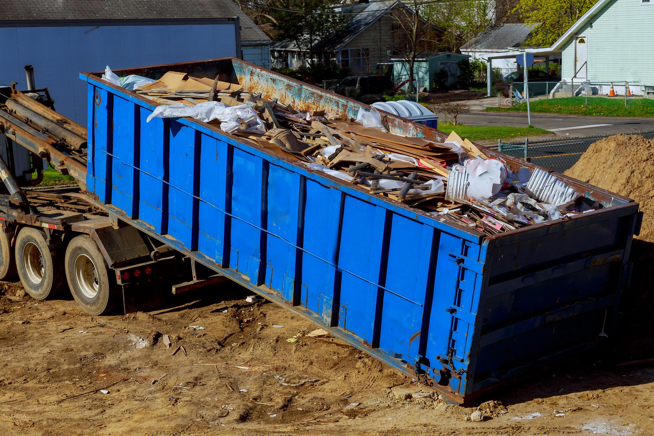 blue roll-off dumpster full of junk